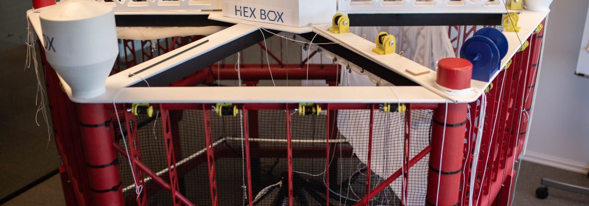 A downscaled model made in wood of Ocean Aquafarms offshore fish farm, named the Hex Box.,